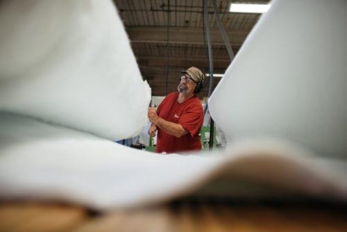 Employee examining white felt
